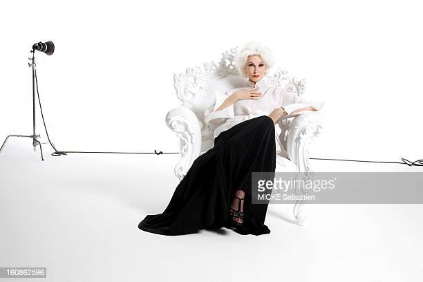 Attitude of the American supermodel Carmen Dell'Orefice photographed in New York dressed in a long black skirt sitting in a chair Styling Rick Ramsey...