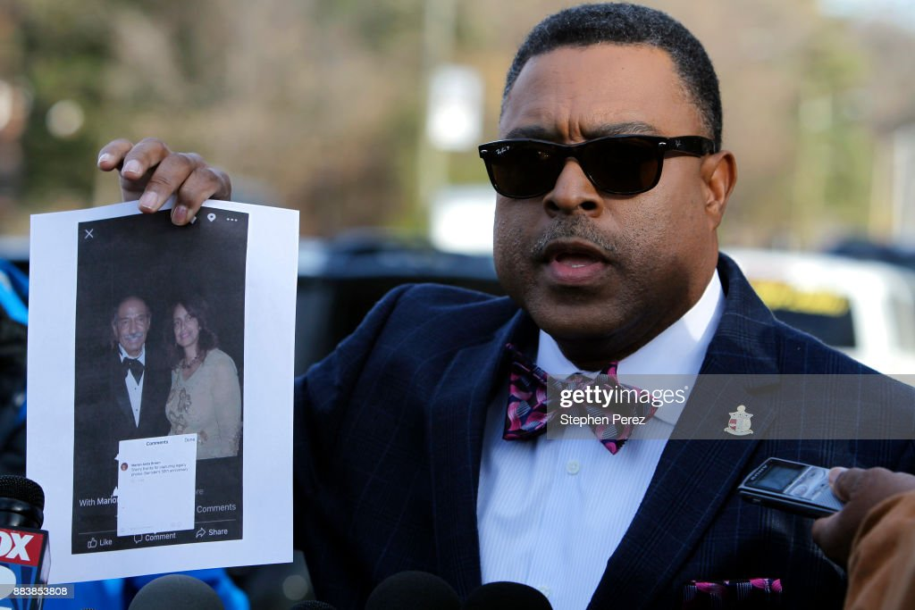 Attorney Arnold Reed displays a photo of Rep. John Conyers and Marion Brown outside Conyers home on December 1, 2017 in Detroit, Michigan. Reed is representing the embattled Michigan Congressman following accusations of sexually inappropriate behavior from former staff member Marion Brown. The photo shows Conyers and Brown attending the 50th Anniversary of the Barristers' Ball in 2011.