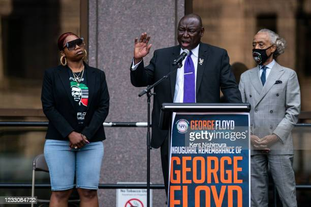 Attorney Ben Crump, center, flanked by Bridgette Floyd, left, and Rev. Al Sharpton, right, speaks during the inaugural remembrance rally and march...