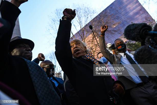 Attorney Benjamin Crump from left, Philonise Floyd , and Reverend Al Sharpton clinch their fist during a news conference for the family of George...