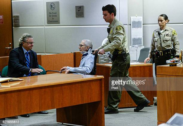 Attorney David Z Chesnoff left looks on as real estate heir Robert Durst in the wheelchair arrives in the Airport Branch of the Los Angeles County...