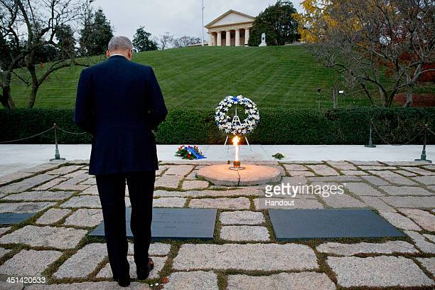 Attorney General Eric Holder bows his head at the grave of US President John F Kennedy at Arlington National Cemetery on November 22 2013 in Arligton...