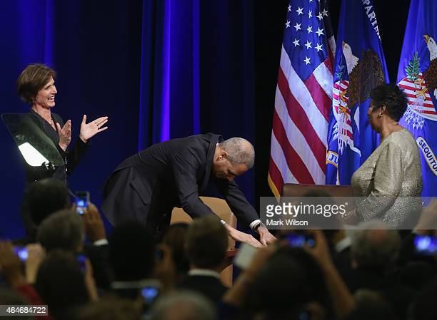 S Attorney General Eric Holder bows to singer Aretha Franklin as acting Attorney General Sally Quillian applauds during a portrait unveiling ceremony...