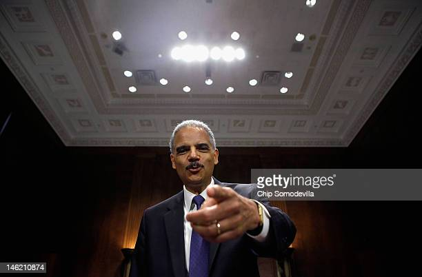 S Attorney General Eric Holder jokes with photographers before testifying to the Senate Judiciary Committee on Capitol Hill June 12 2012 in...