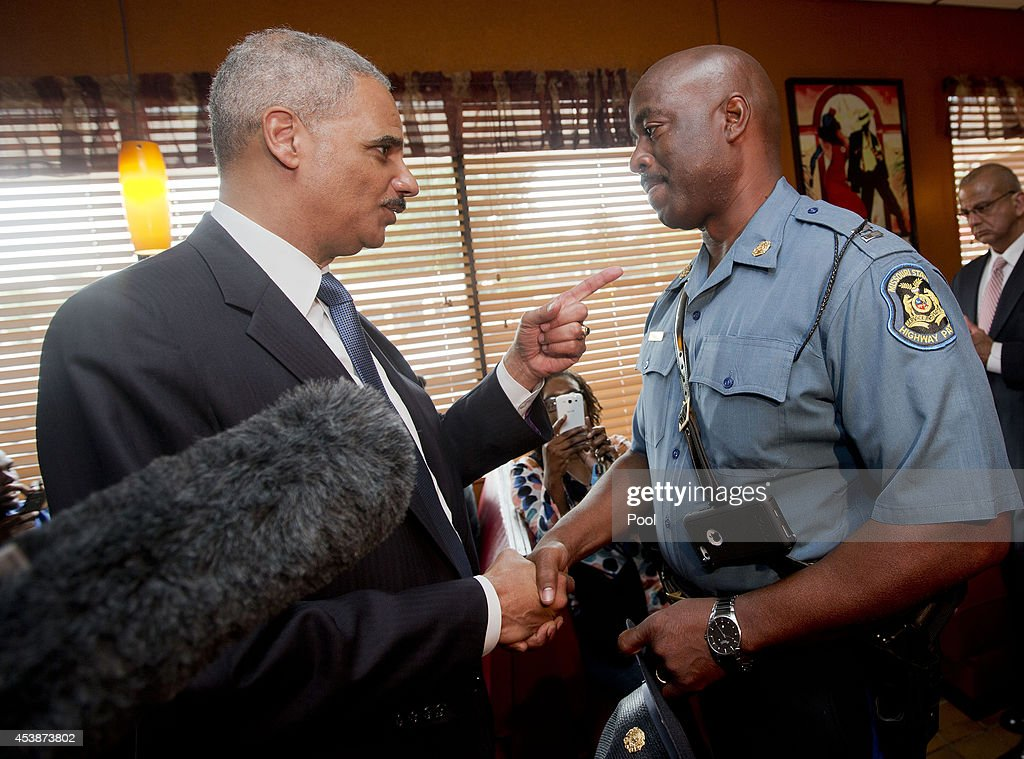 U.S. Attorney General Eric Holder (L) talks with Capt. Ron Johnson, right, of the Missouri State Highway Patrol at Drake's Place Restaurant,August 20, 2014 in Florrissant, Missouri. Holder is traveling to Ferguson, Mo., to oversea the federal government's investigation into the shooting of 18-year-old Michael Brown by a police officer on Aug. 9th. Holder promised a 'fair and thorough' investigation into the fatal shooting of a young blackman, Michael Brown, who was unarmed when a white police officer shot him multiple times.