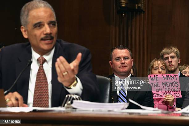 S Attorney General Eric Holder testifies before the Senate Judiciary Committee as Code Pink demonstrator Medea Benjamin protests against the use of...