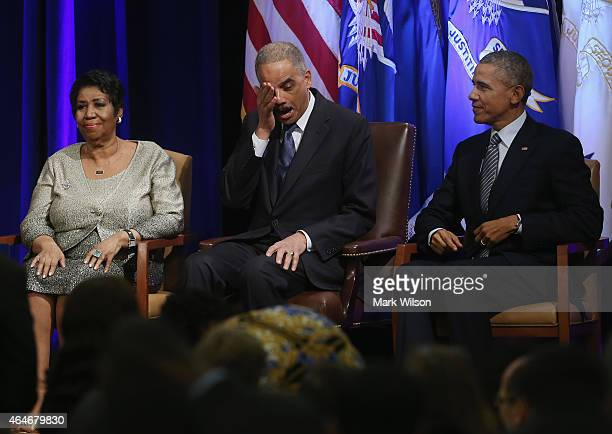 S Attorney General Eric Holder wipes away tears while seated next to US President Barack Obama and singer Aretha Franklin who just finished singing...