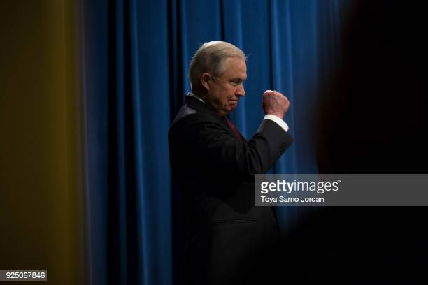 Attorney General Jeff Sessions holds up a fist during a press conference at the Department of Justice in Washington DC on February 27 2018 Sessions...