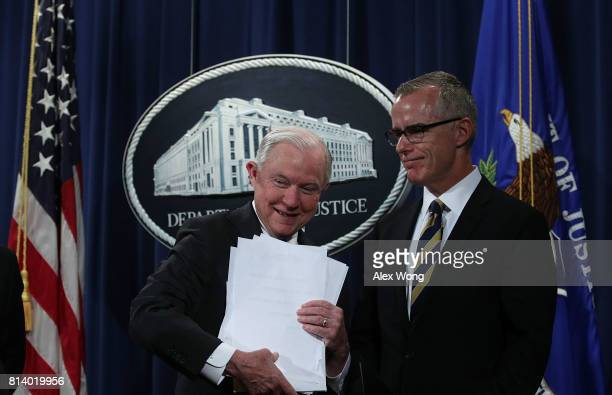 S Attorney General Jeff Sessions picks up his remarks as Acting FBI Director Andrew McCabe looks on during a news conference to announce significant...