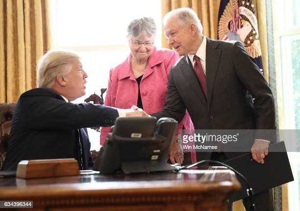 S Attorney General Jeff Sessions shakes hands with US President Donald Trump after Trump signed three executive orders following the swearing in...