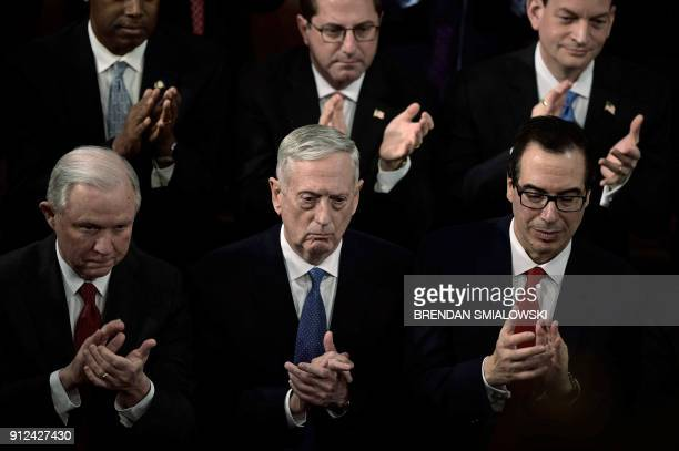 US Attorney General Jeff Sessions US Secretary of Defense James Mattis and US Secretary of Treasury Steven Mnuchin clap as US President Donald Trump...