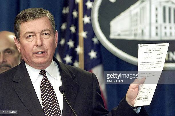 Attorney General John Ashcroft holds up the twelve page criminal complaint filed with the United States Eastern District Court of Virginia against...