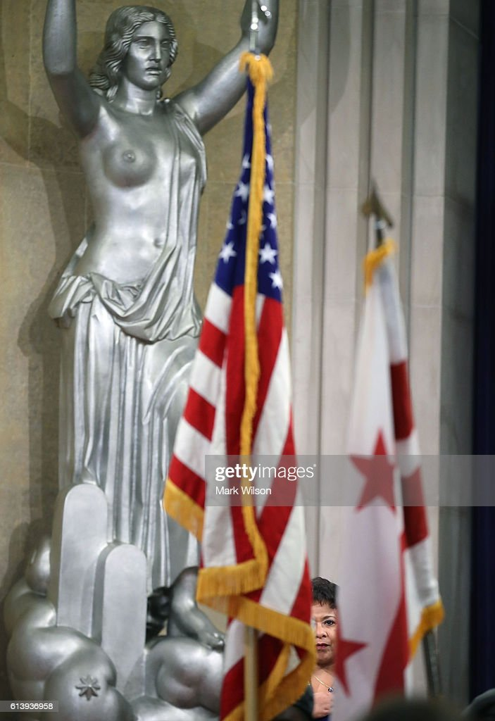 U.S. Attorney General Loretta is partially obscured by flags while participating in the annual Justice Department Hispanic Heritage Month program, at the Justice Department October 11, 2016 in Washington, DC. During Hispanic Heritage month the federal government and communities across the country take time to acknowledge the contributions of Hispanic Americans to the nation.