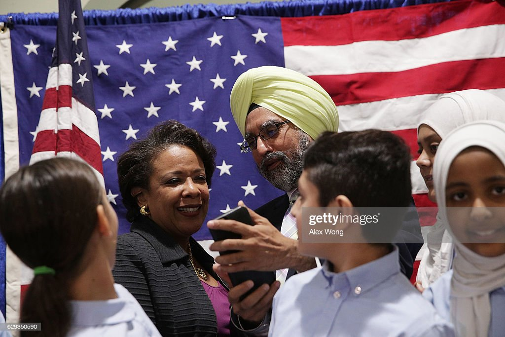 U.S. Attorney General Loretta Lynch (L) shares a moment with Rajwant Singh (R), founder and chairman of the Sikh Council on Religion and Education (SCORE), during an event at All Dulles Area Muslim Society (ADAMS) Center December 12, 2016 in Sterling, Virginia. Lynch spoke to religious leaders and community members about the Department of Justice's efforts to combat hate crimes.