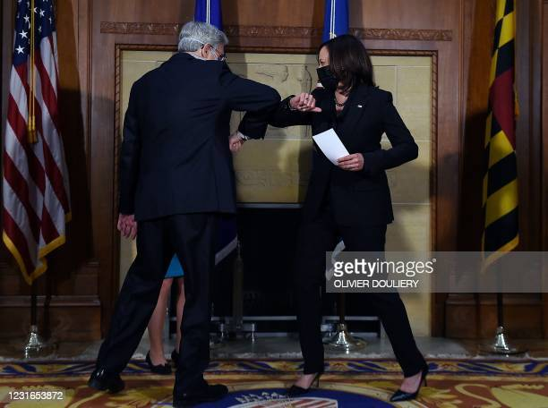 Attorney General Merrick Garland elbow bumps US Vice President Kamala Harris after being ceremonially sworn in at the US Justice Department on March...