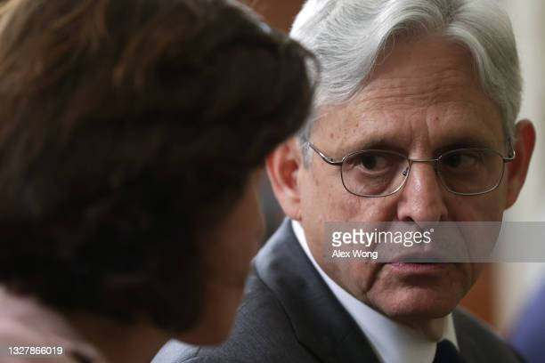 Attorney General Merrick Garland talks to Secretary of Commerce Gina Raimondo as they wait for the beginning of an event at the State Dining Room of...