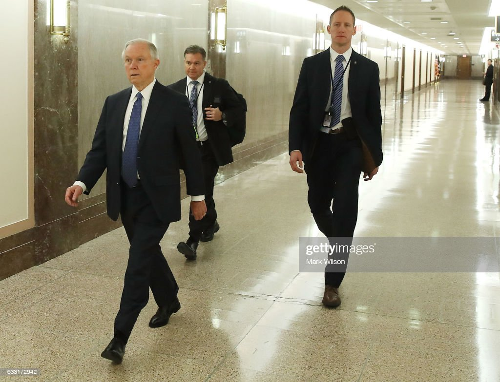 Attorney General nominee, Sen. Jeff Sessions (R-AL), (L) walks with a security detail to a Senate Energy and Natural Resources committee hearing on Capitol Hill, January 31, 2017 in Washington, DC. The committee met to vote on the nomination of Rep. Ryan Zinke (R-MT) to be Interior Secretary, and former Gov. Rick Perry (R-TX) to be Energy Secretary.