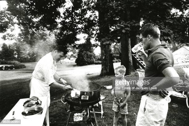 US Attorney General Robert F Kennedy drinks from a glass as he along with a young boy watch an unidentified man in an apron grills hamburgers on a...