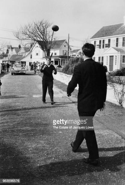 US Attorney General Robert F Kennedy keeps his eys on a football thrown by his brother lawyer Ted Kennedy on a residential road Hyannis Port...