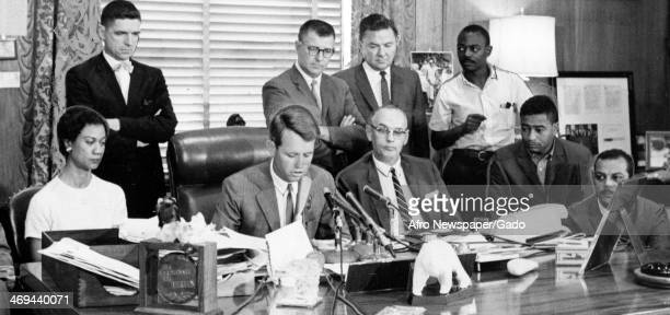 Attorney General Robert Kennedy with Gloria Richardson civil rights activist and a group of men seated at a desk with microphones during the...