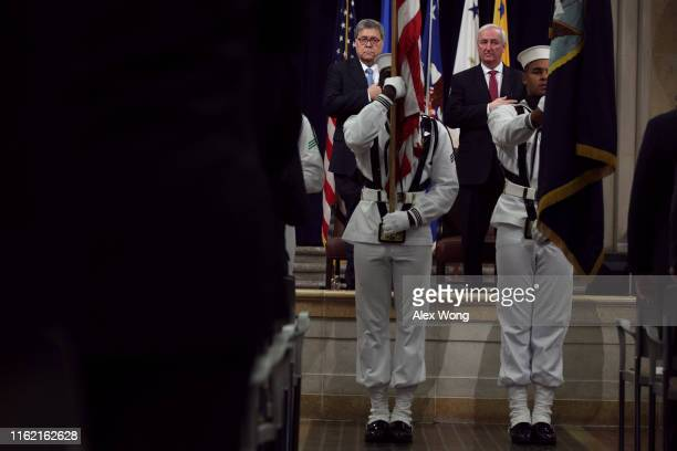 S Attorney General William Barr and Deputy Attorney General Jeffrey Rosen listen to the national anthem behind a color guard during a Combating...