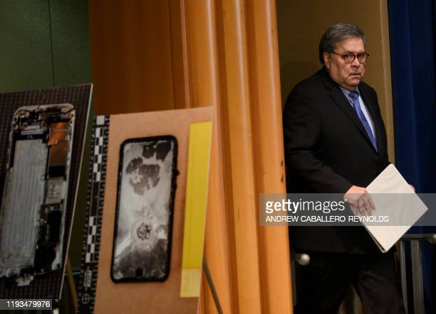 US Attorney General William Barr walks past diplayed pictures of the shooter's cellphone as he arrives at a press conference regarding the December...