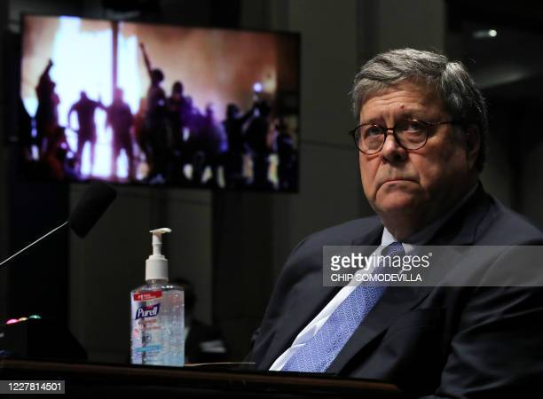 Attorney General William Barr watches a Republican Exhibit video of people rioting during the House Judiciary Committee hearing in the Congressional...