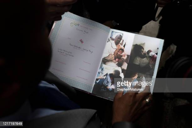 Attorney L Chris Stewart holds a family album filled with images of George Floyd with his daughter Gianna Floyd and her mother Roxie Washington are...