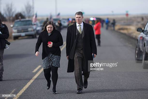 Attorney Mike Arnold who is representing organizer Ammon Bundy and a colleague walk along a road lined with media and protestors at the Malheur...