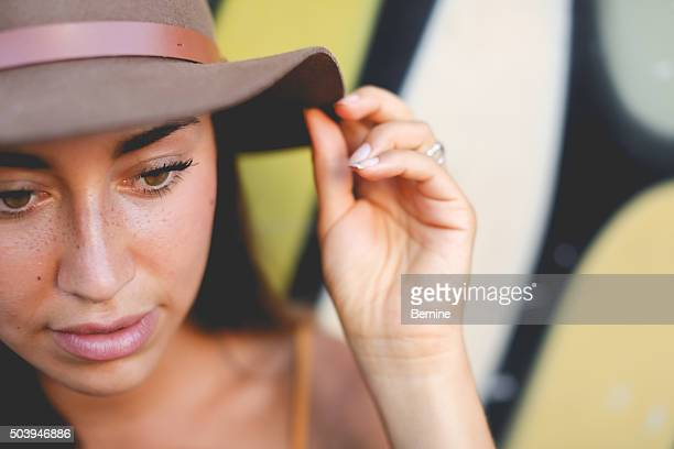 Attract young brunette female touching the rim of her hat