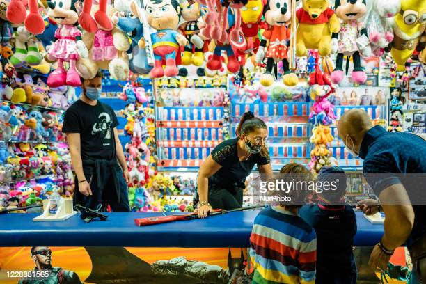 Attraction workers at work while children play at the Luna Park in Molfetta at Secca dei Pali on October 3 2020 First day of opening of the Luna Park...