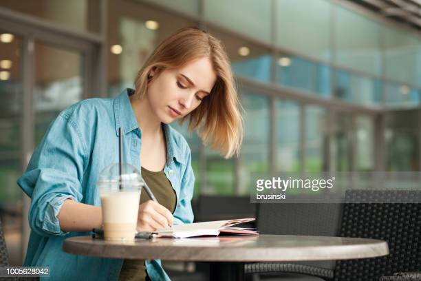 attractive 20 year old woman draws in a sketchbook