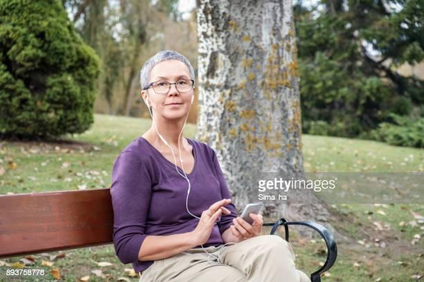 Atractiva mujer de 50 años de edad, sentado en el parque público con teléfono