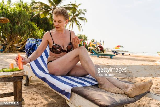 attractive active 50-years-old european woman, a tourist, is resting in a chaise lounge on a beach in bentota, sri lanka. she is applying sunscreen cream on her skin, when a beach worker is working in the backdrop. - 25 29 years stock pictures, royalty-free photos & images