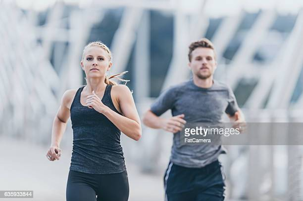 Attractive adult couple out running together across a city bridge
