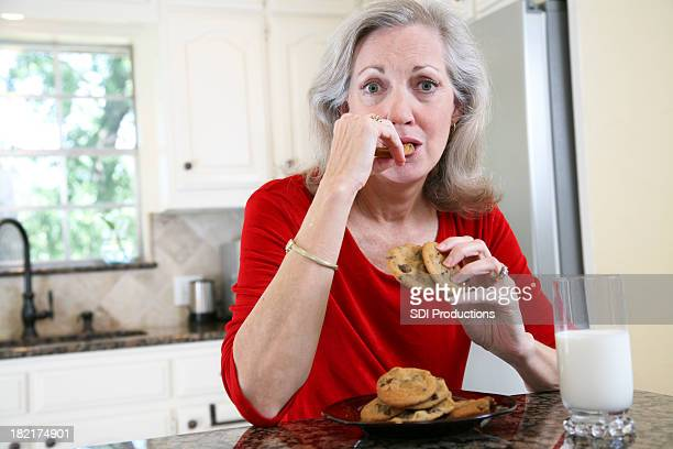 Attractive Adult Female Eating Cookies and Milk with Copy Space