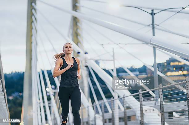 attractive adult female running over a bridge at dusk - women wearing spandex stock photos and pictures
