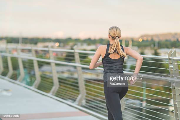 Attractive adult female running over a bridge