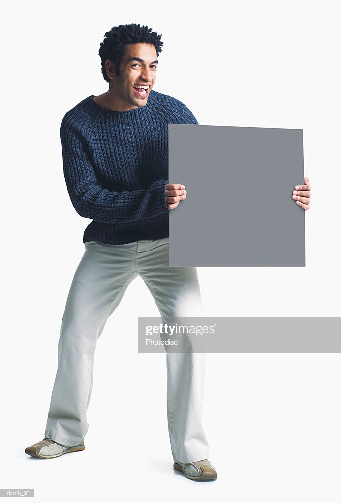 attractive african american man wears khaki pants grey sweater holds blank sign smiles enthusiasm : Stockfoto