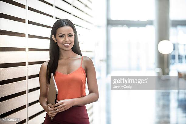 Attractive African businesswoman with long dark hair holding laptop.