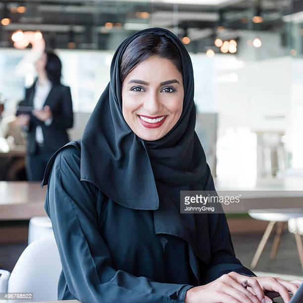 attractive arab businesswoman wearing hijab smiling towards camera - united arab emirates stock pictures, royalty-free photos & images