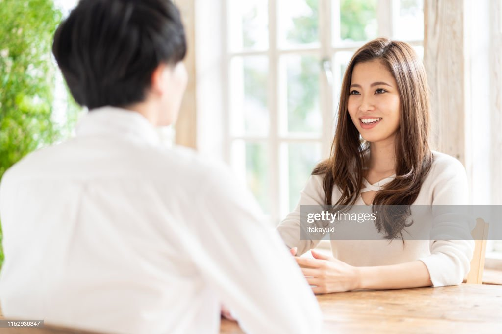 attractive asian couple talking in living room : Stock Photo