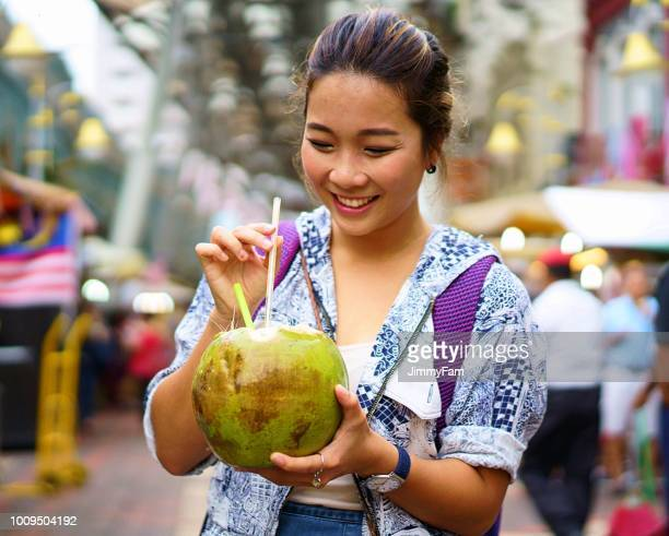 attractive asian female tourist enjoying a coconut drink at an asian street market in malaysia - southeast stock pictures, royalty-free photos & images