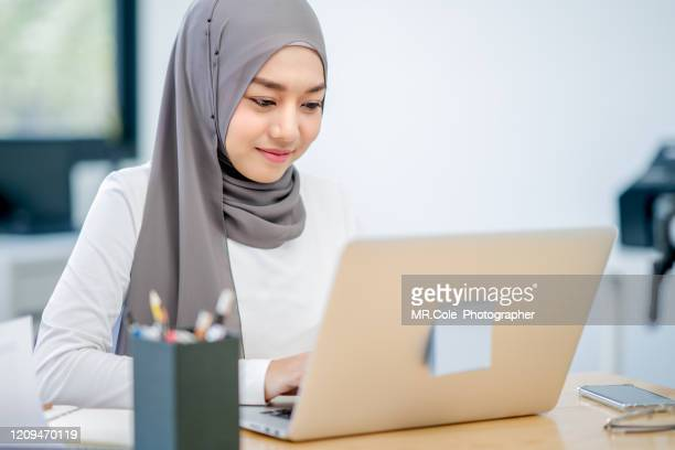 attractive asian muslim woman working using laptop in modern office,modern muslim woman muslim women from the south east and east asian region lifestyle - religious dress stock pictures, royalty-free photos & images