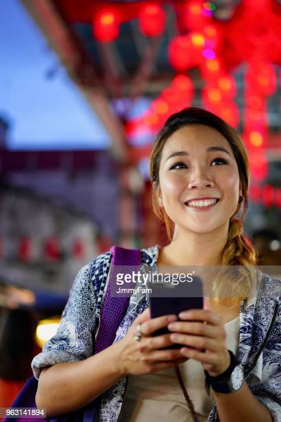 attractive asian woman exploring asian night market, searching information on smartphone. - malaysia beautiful girl stock photos and pictures