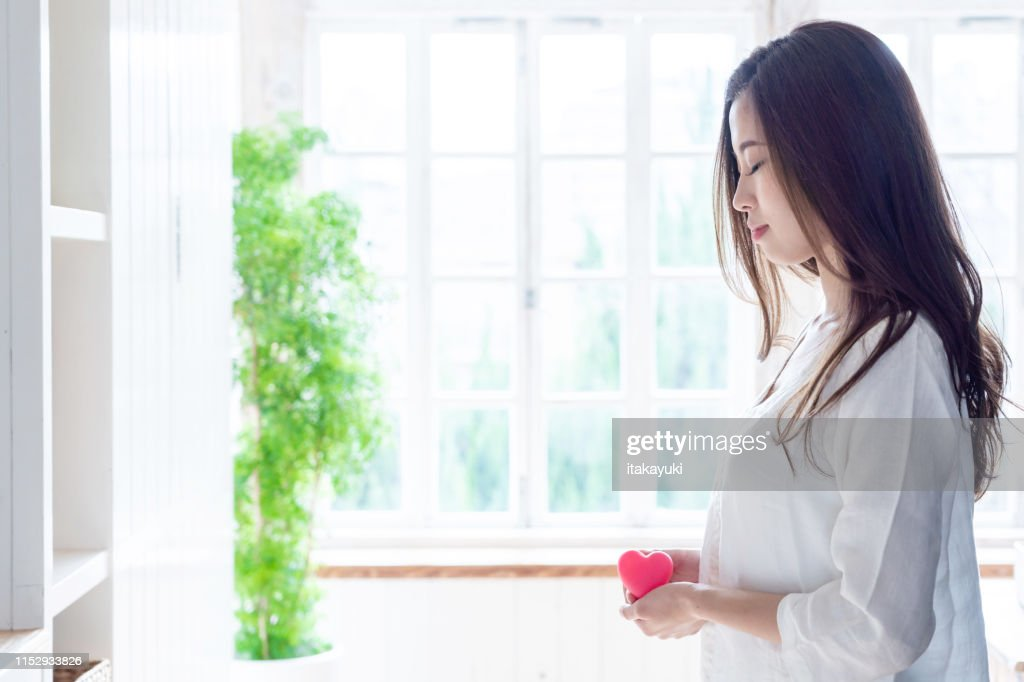 attractive asian woman holding heart symbol : Stock Photo