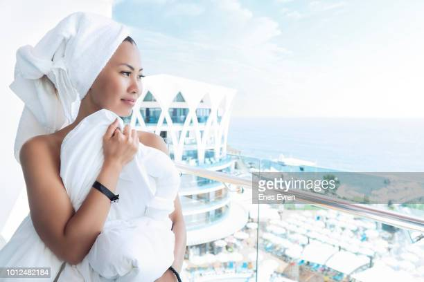 Attractive Asian Woman in towel looking out from the balcony - Luxury Hotel Concept