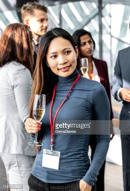 aantrekkelijke aziatische vrouw met een glas champange met medewerkers op een achtergrond - like button stockfoto's en -beelden
