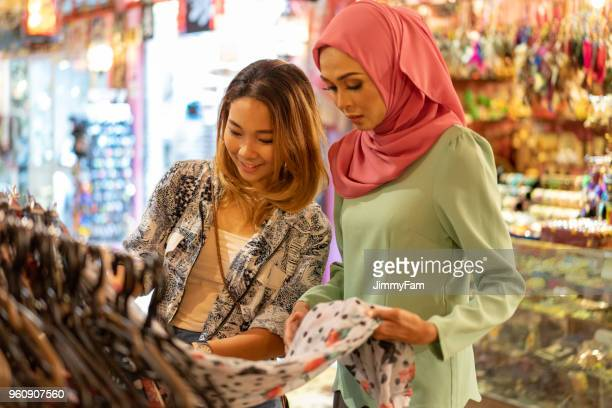 Attractive Asian Young Friends shopping in a Bazaar.