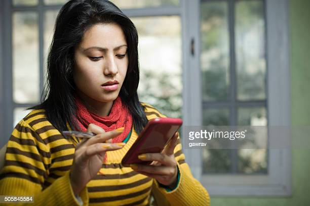 Attractive, Asian, young woman using phablet.